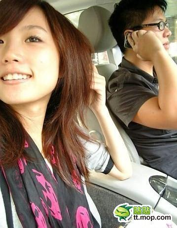 Chinese girl riding in passenger seat next to driver on mobile phone.