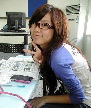 Pretty Shanghai University female student at her desk with peace sign.
