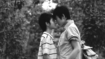 Two Chinese boys embracing each other in the streets.