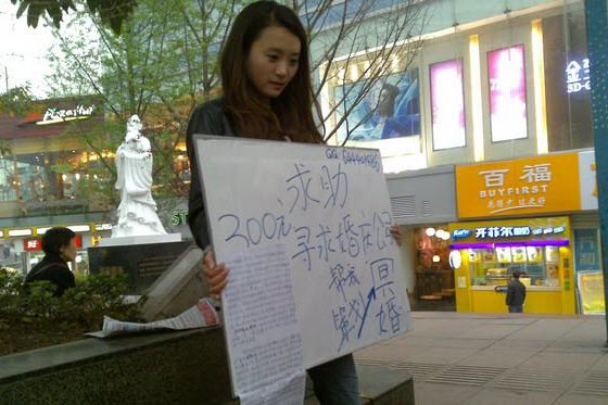 Girl holds sign seeking marriage with the dead.