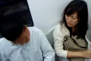 Man and woman argue on Beijing subway.