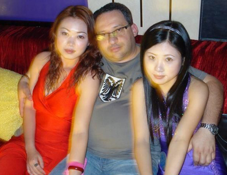 Man with Chinese girls in both arms.