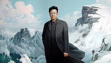 Kim Jong Il wearing black in front of snowy mountains.
