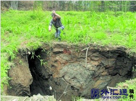 A Chinese man measures the depth of a sinkhole with string.