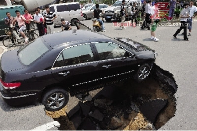 A car stuck above a sinkhole that formed underneath the road.