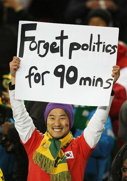 South Korea fan shows sign asking people to foreget politics for 90 minutes.