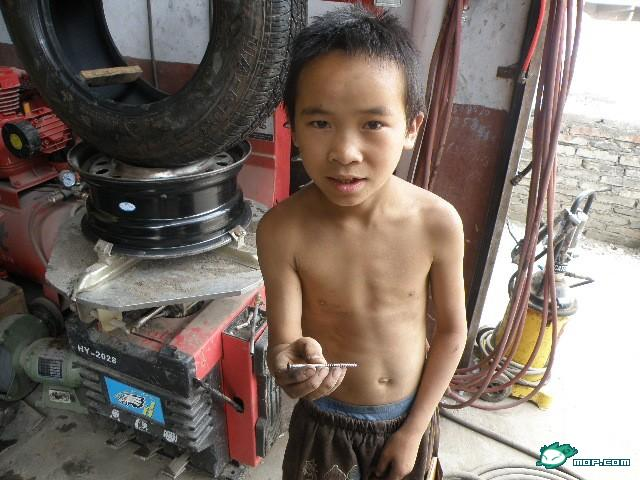 A 10-year-old Chinese boy holds a screw.
