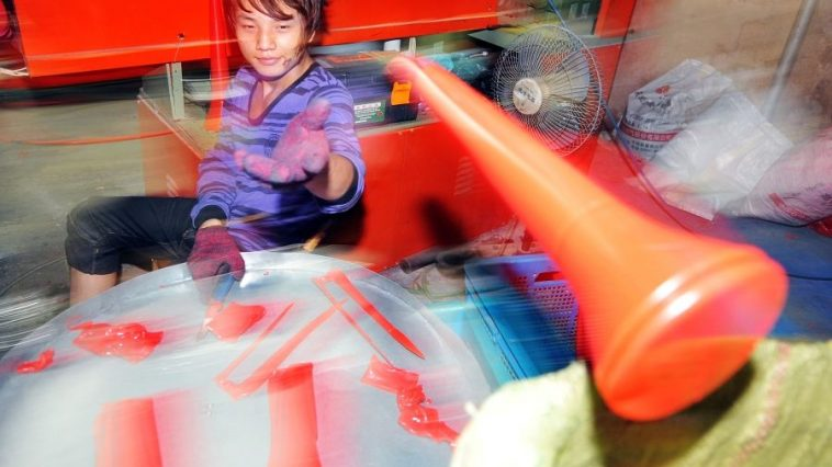 Chinese worker making Vuvuzela horns in Zhejiang province, China.