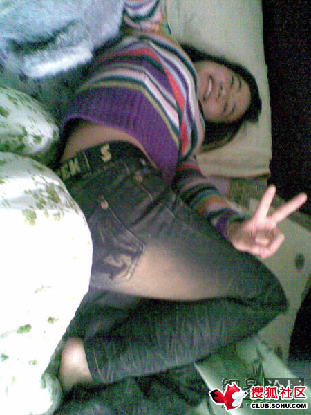 Chinese girl on bed with peace sign.