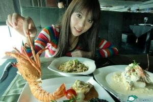 Chinese girl holding a lobster at a restaurant.