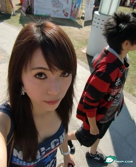 Chinese girl taking a self-photo on the street.