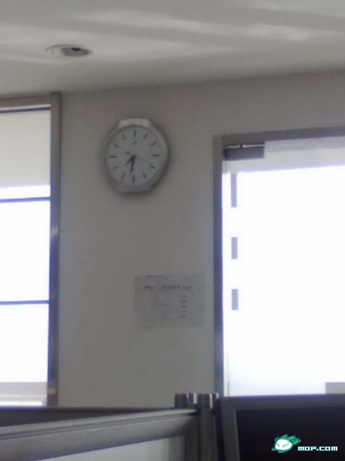 A clock hangs on the wall of an office.