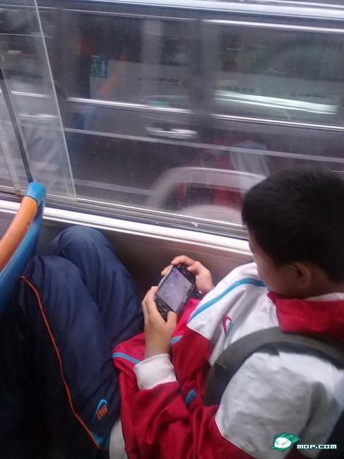 A young Chinese schoolboy plays with his PSP on his bus ride home.