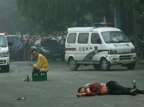 In Liaoning, China, a policeman lies on the street having been stabbed to death while his assailant sits on a beer crate at a distance.
