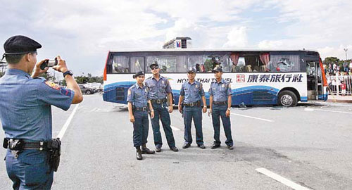 Philippine police taking photos in front of the Hong Kong tour bus that was involved in a hostage crisis.