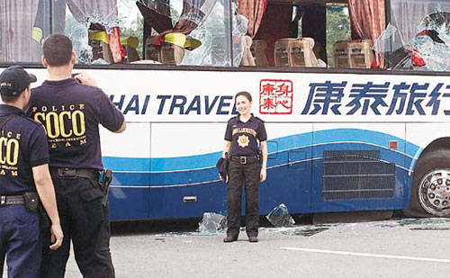A policewoman takes a photo in front of the disabled Hong Kong tour bus that was involved in a hostage crisis.