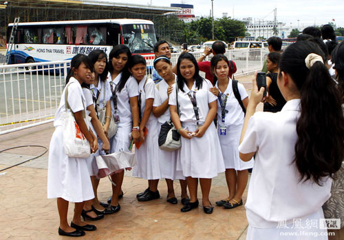 Philippine schoolgirls taking a group photo in front of the disabled Hong Kong tour bus that was involved in a hostage crisis.