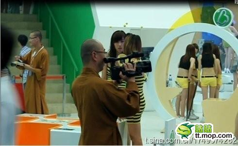 A monk uses a high-end digital camera while young, attractive girls wearing form-fitting dresses and hot pants fill the background