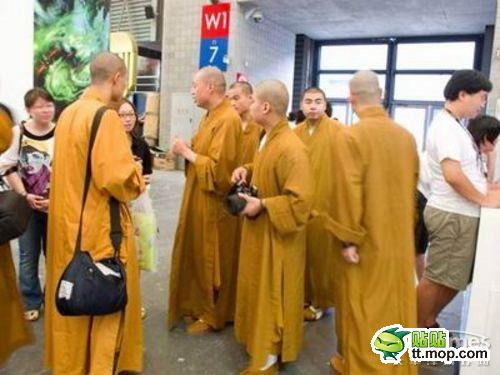 Monks chatting with other patrons of ChinaJoy, possibly to find out when the next show of dancing girls is starting