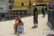 Two Chinese men crawling on their knees on a pedestrian overpass in Shenzhen, China.
