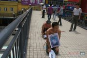 Chinese man passes out leaflets searching for his wife in Shenzhen, who left him with their child.