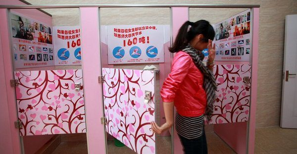 An embarrassed Chinese student exits from a standing female urinal.