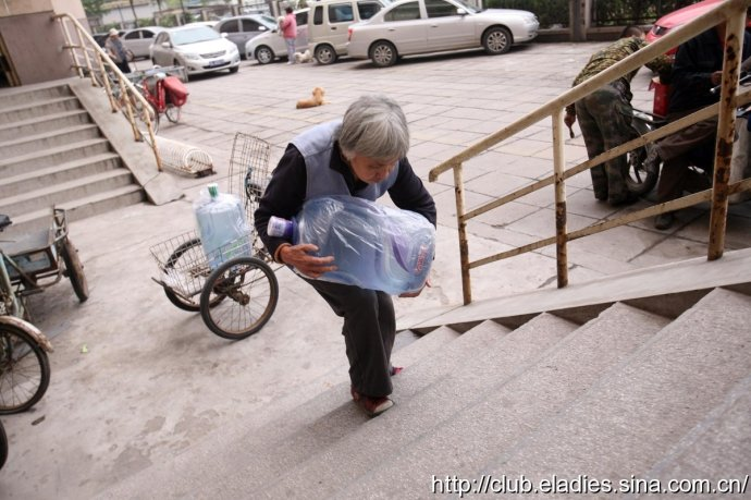 An old Chinese lady in her 70s delivers water in China to support her family.