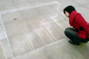 "3D chalk art in China: A girl looks down a ""stairwell"" drawn on the concrete ground."