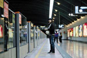 A girl standing on a subway platform.