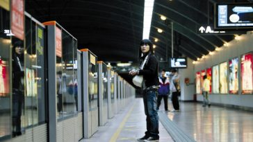 A girl standing on a subway platform.