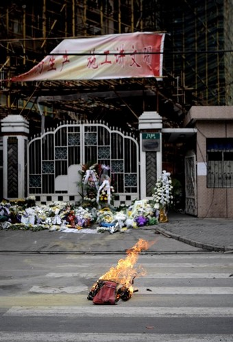 This photo taken on November 17, 2010 shows flowers and offerings (burning) at an entrance gate to a high-rise where 53 people died on November 15 in a fire in Shanghai. China on November 17 ordered a nationwide overhaul of fire-control measures after the blaze at the Shanghai high-rise killed 53 people and highlighted the country's chronic problem with lax safety enforcement.    CHINA OUT   AFP PHOTO (Photo credit should read STR/AFP/Getty Images)