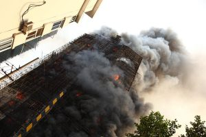 Thick black smoke envelope a burning residential building in Shanghai's Jing An district.