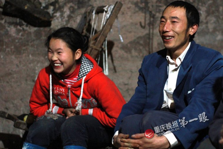 16-year-old Wen Wen sits beside her possible husband, 34-year-old Deng Changjiang.