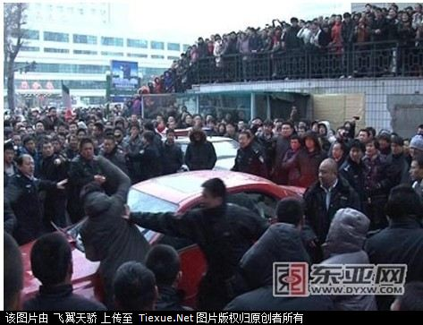 A mob surrounds a Mazda6, the driver having hit an old lady and then beat her.
