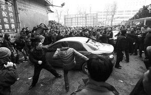 Members of the angry crowd kicking at the Mazda6 after the driver hits and old lady and then beats her.