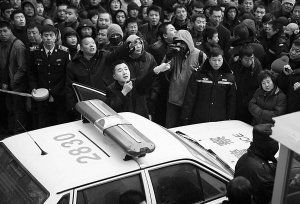 A Chinese police officer uses a loud speaker begging the crowd to remain calm.
