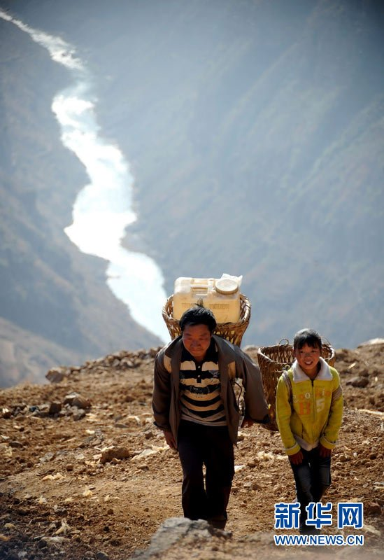Ding Chaoke and his daughter carry water on back to their home (March 7). They are villagers from Chahe Village located in Malu Town of Huize County in Qujing City of Yunnan Province, which has become a disaster area. The local villagers must climb over a mountain to reach a water source to get water. Xinhua reporter Qin Qing