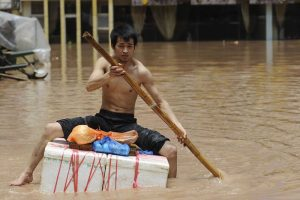 "In Sichuan Province's Dazhou City county seat, a man rows forth on his an improvised ""boat"" (July 19). On July 16th, Sichuan Province's Dazhou City suffered torrential rains and flooding, the Qu River water level rising 24.8 meters, 9.31 meters beyond the warning level, with over 1/3 of the city submerged. Photo: Xinhua reporter Jiang Hongjing"