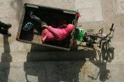 A mentally disabled man lies in a motorized tricycle.