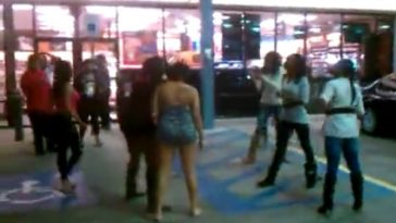 American black women get into a fight in front of a gas station.
