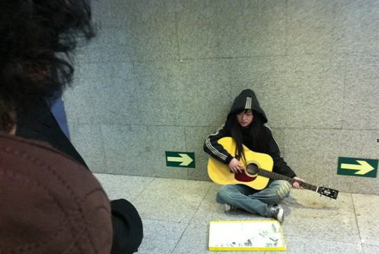 """""""Beggar Loli"""", China's latest internet celebrity, a street musician, singing songs for 1 RMB each in a pedestrian tunnel in Beijing, China."""