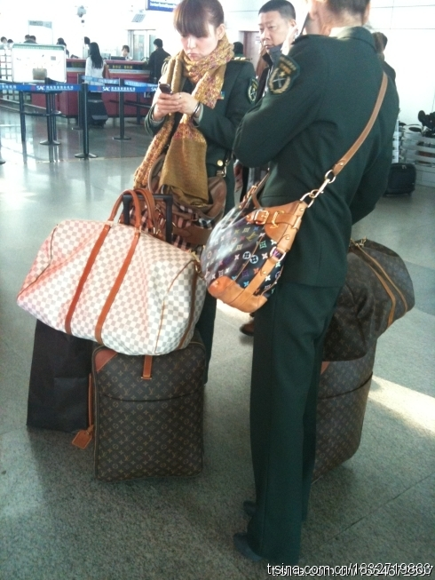 Chinese female soldiers traveling with Louis Vuitton bags and suitcases.