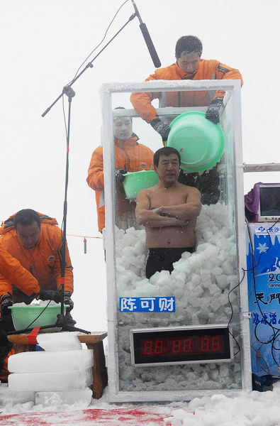 Event staff dump ice into Chen Kecai's ice booth.