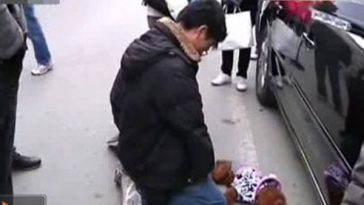 In Suzhou China, a young man is forced to kneel before a dog on the street he had accidentally hit and killed as compensation to the dog's owner.