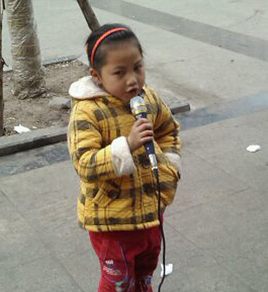 A little girl singing songs for money on Beijing Road in Jingzhou of Hubei province.