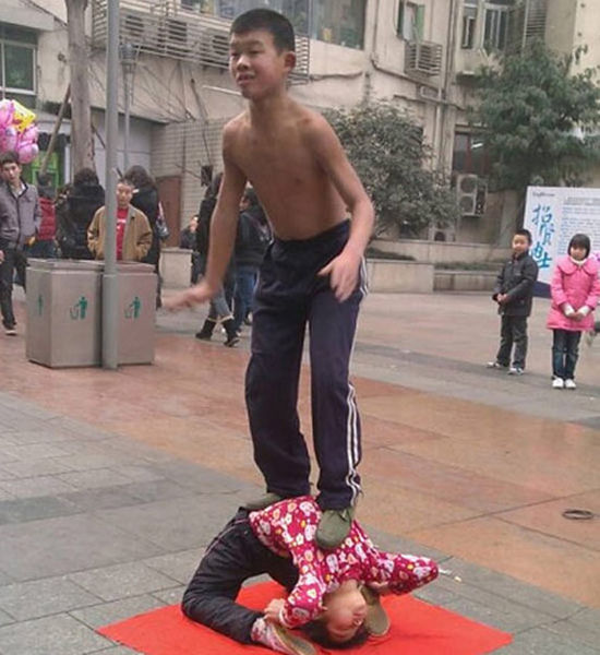 2011 February 8th around 16:00, location of shot: Chongqing City Jiulongpo District Yangjiaping Pedestrian Street Xichengtian Street Shopping Center, two little boys around 10-years-old, a girl about six or seven years old, perform acrobatics on the street.