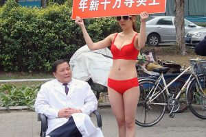 In China, a psychologist advertises himself on the side of a street with the help of a model wearing only red underwear holding a sign.