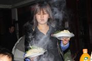 Chinese waitress at hot pot restaurant with a cigarette dangling from her lips and a strange vacant look in her eyes.
