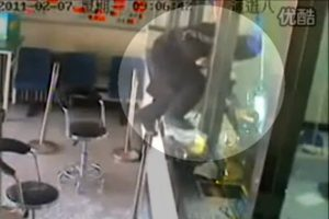 In Baodi, Tianjin, China, a bank robber uses a hammer/hatchet to smash through the reinforced glass at a postal savings bank.