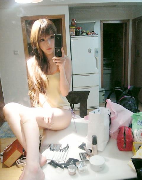 Wang Jiayun sitting on a table taking self-photos.